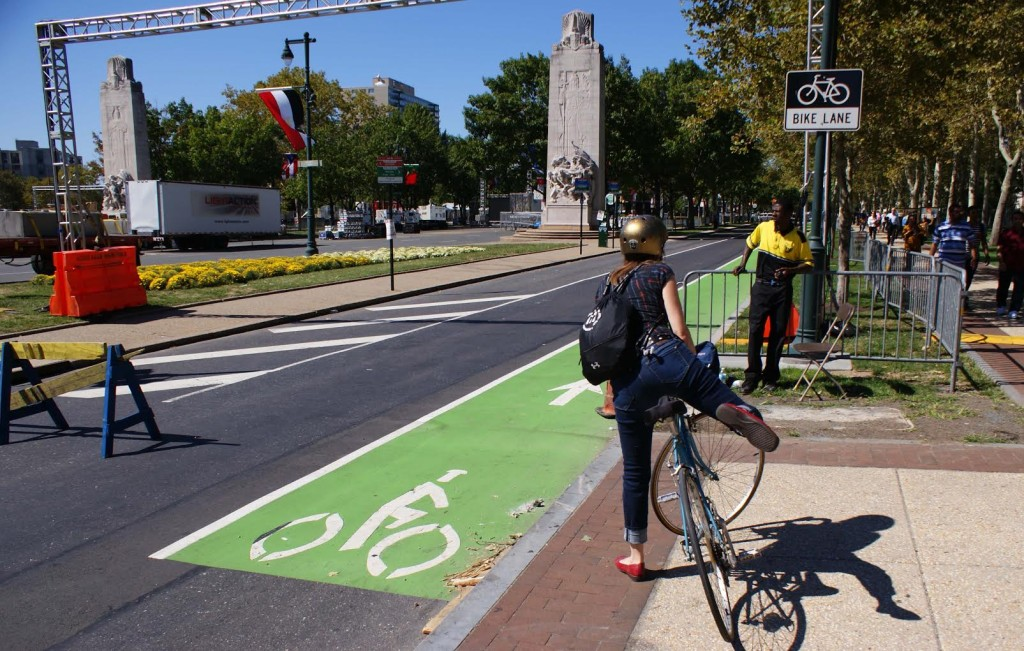 A security officer asks a cyclist to use the sidewalk next to the Benjamin Franklin Parkway.