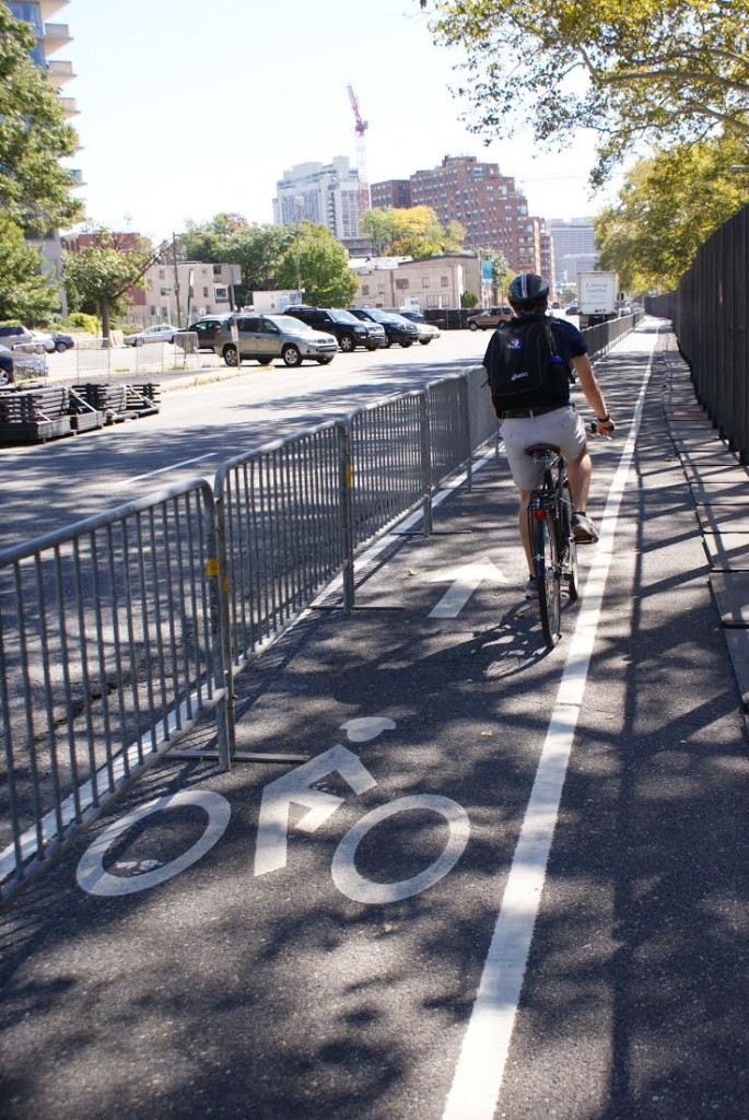 A cyclist travels in the bike lane on Pennsylvania Avenue between barriers.