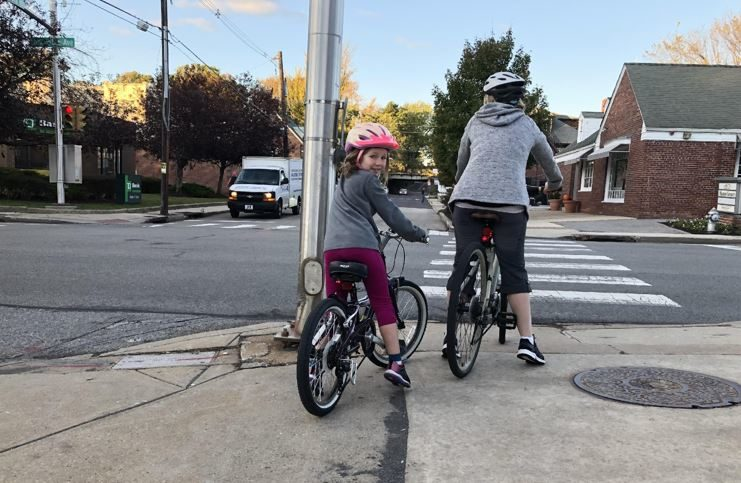 Young girl riding bike with an adult in a neighborhood..