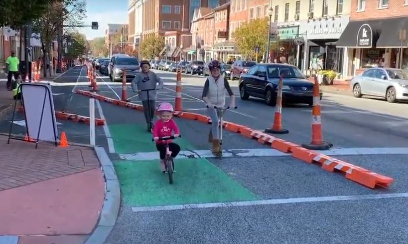 Children and adult biking along the temporary protected bike lane during day of demonstration.