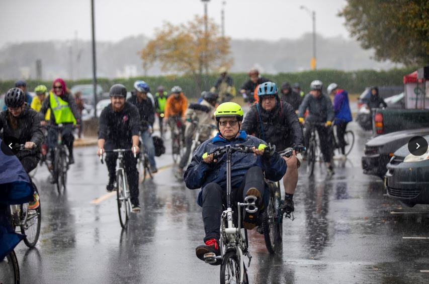 Group of over 15 cyclist biking in the rain.