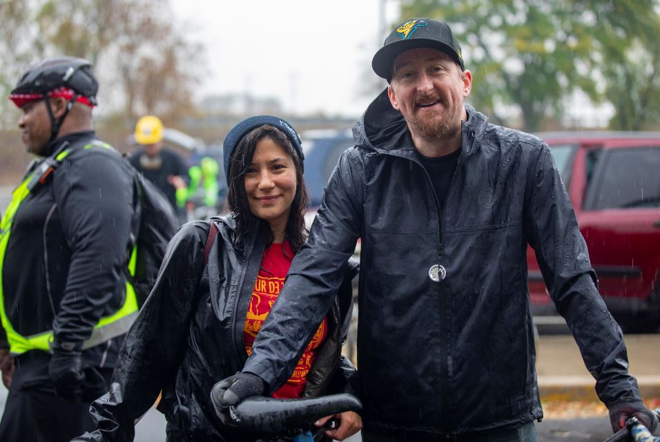 Two people with their bikes smiling in the rain.