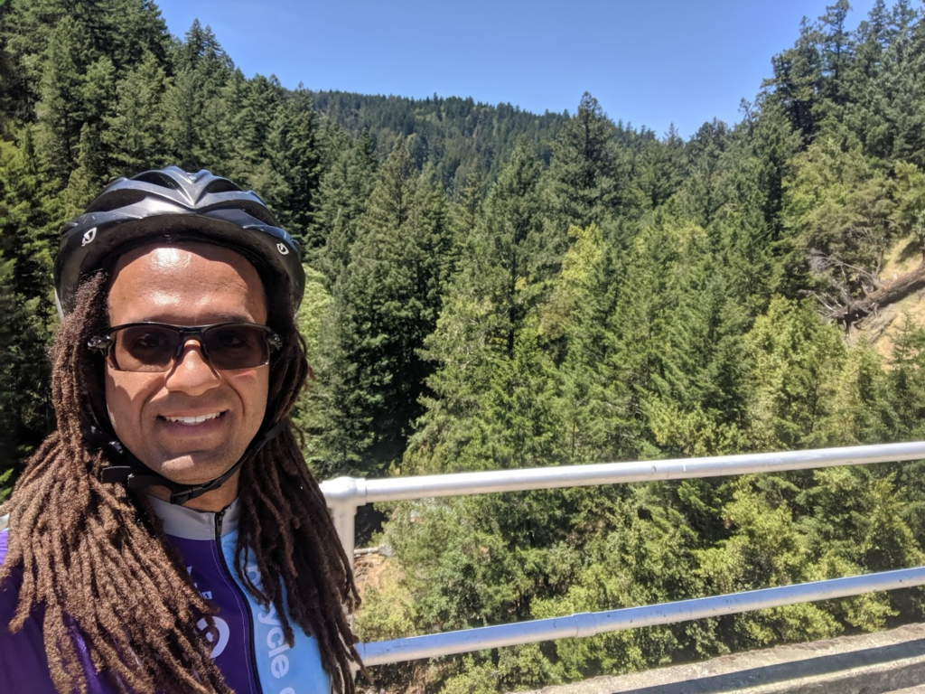 Bicycle Coalition member Ryan Sullivan rocking a helmet in front of a beautiful landscape of trees