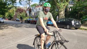 cyclist wearing mask rides towards the camera on a leafy boulevard