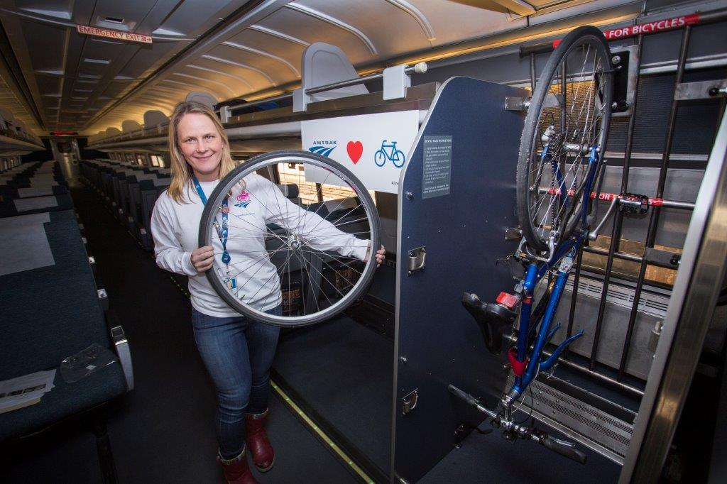 An Amtrak staffer demonstrates wheel removal for hangin your bike on the train.